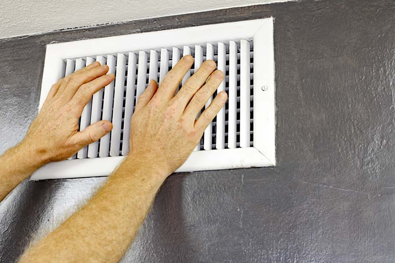 hands in front of white wall air vent