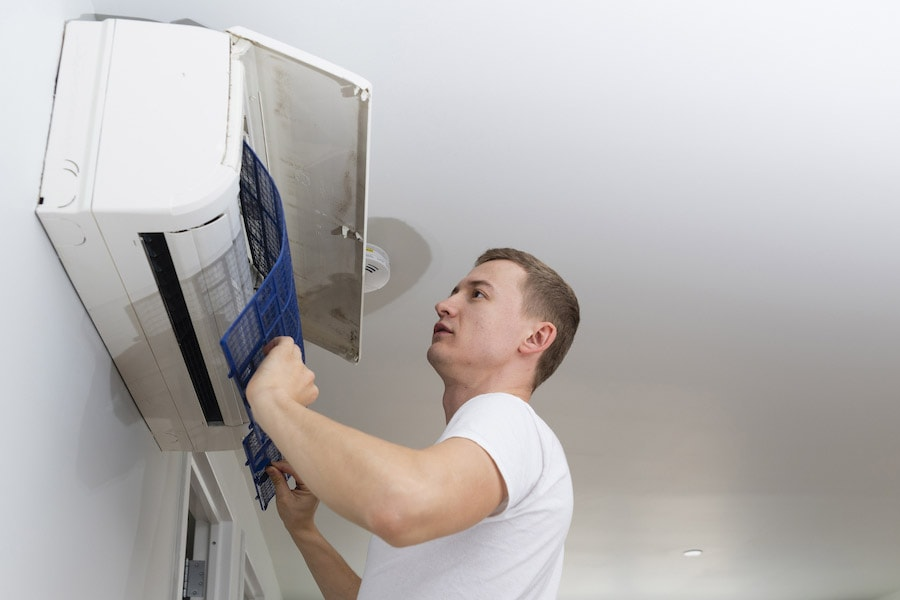 The young man cleaning filters in the air-conditioning split device, The Problem With Clogged Air Filters | Indoor Air Quality, Maintenance